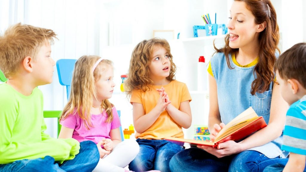 woman telling a story to 4 children