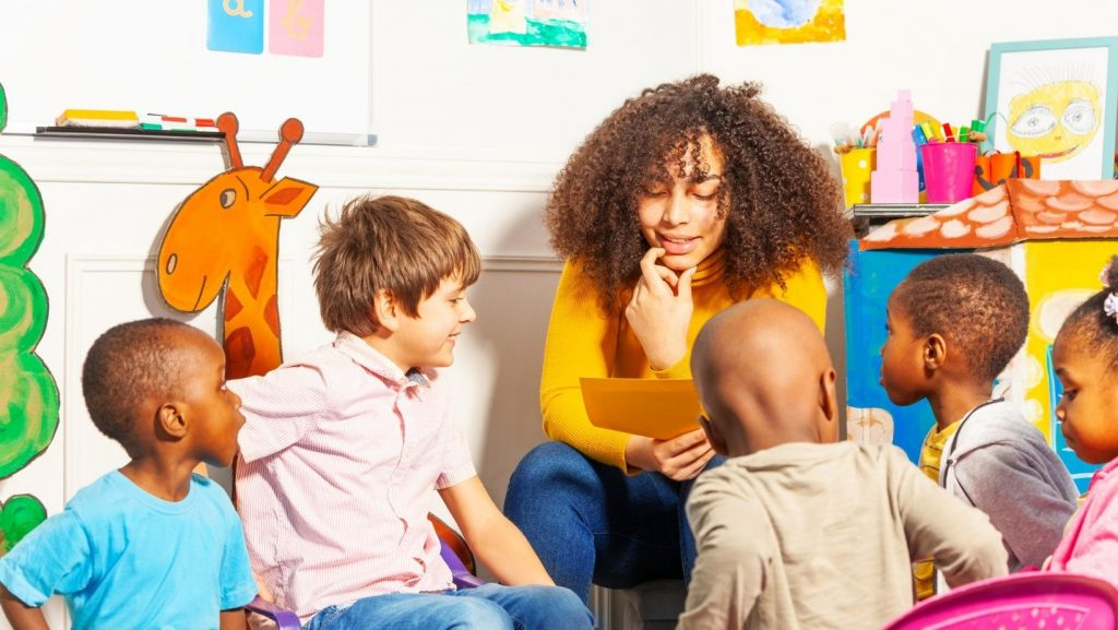 woman of color telling a story to diverse children