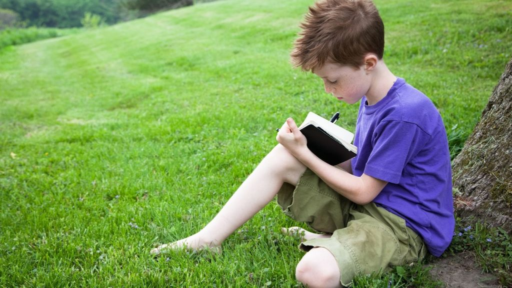 boy writing in journal under a tree
