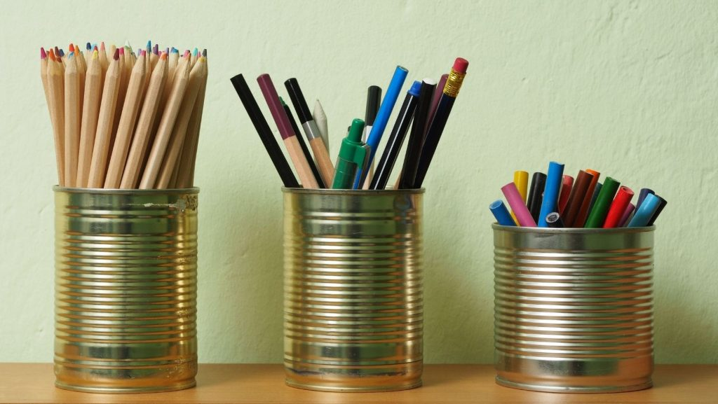 pens and pencils in upcycled tin cups